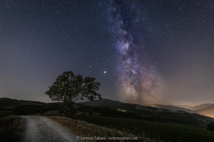 La Via Lattea da via Valla (Sant'Ilario Baganza) Sulla sinistra si distinguono i pianeti Saturno e Giove. Dati di scatto: 21/8/2020 ore 23:33 Per il cielo: ISO 400; f/2,8; 180 sec @ 17 mm con astroinseguitore Minitrack LX2. Per il terreno: ISO 400; f/2,8; 180 sec @ 17 mm.